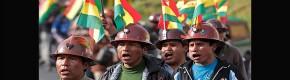 Mineros marchando con la bandera de Bolivia en su casco
